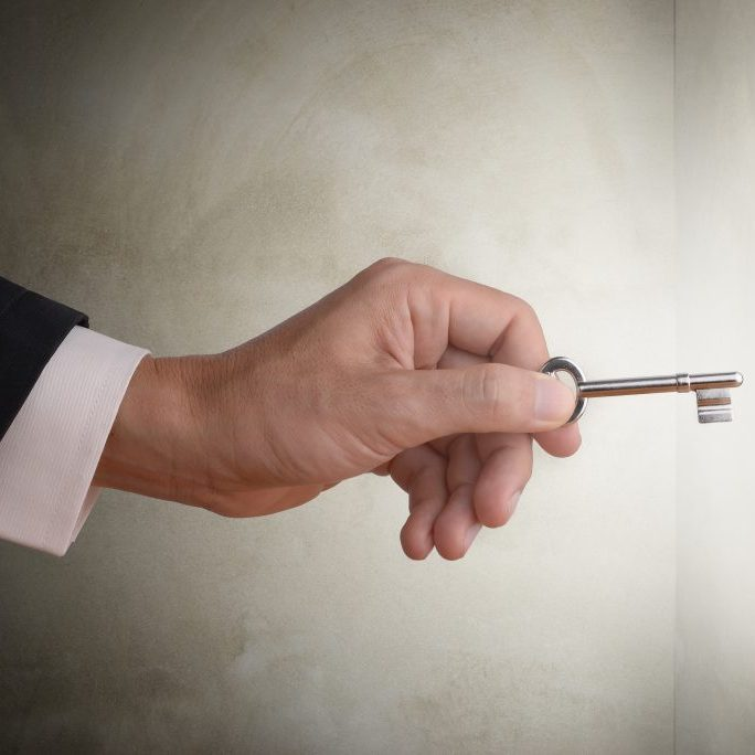 Business man hand holding key to the hole to unlock the secret, abstract business concept to solve problem, find solution, get success or find key strategy. Dark tone with concrete wall background and glow light effect.