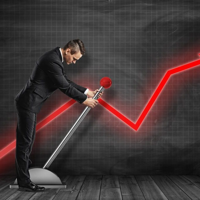 Side view of businessman looking down and pulling big lever near black graph ruled wall with red graph arrow on it. Jumpstart your business. Work hard. Achieve success.