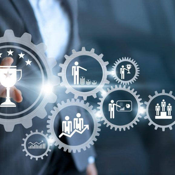 Business mechanism concept. Businessman touching trophy winner successful and business processes workflows in gears icons on virtual screen